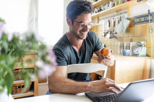 Happy man sitting at table in kitchen using laptop - KNSF07656