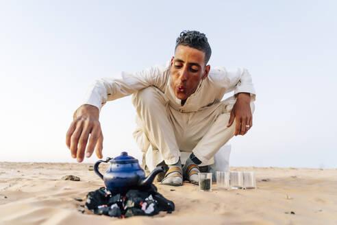 Man preparing tea in Sahara desert, Tindouf, Algeria - OCMF01057