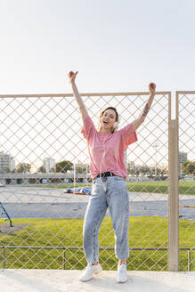 Happy young woman listening to music at a wire mesh fence - AFVF05489