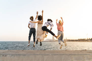 Carefree friends jumping on a quay wall - AFVF05501