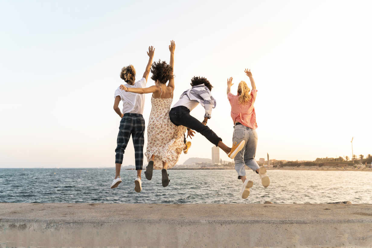 Carefree friends jumping on a quay wall - AFVF05501 - VITTA GALLERY/Westend61