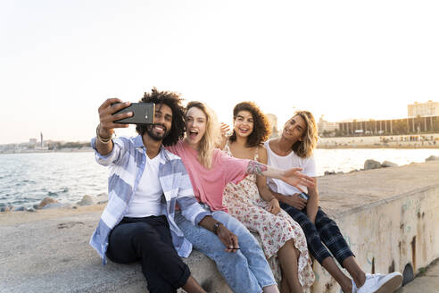 Happy friends sitting on quay wall at sunset taking a selfie - AFVF05507