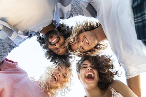 Portrait of happy friends huddling outdoors - AFVF05513