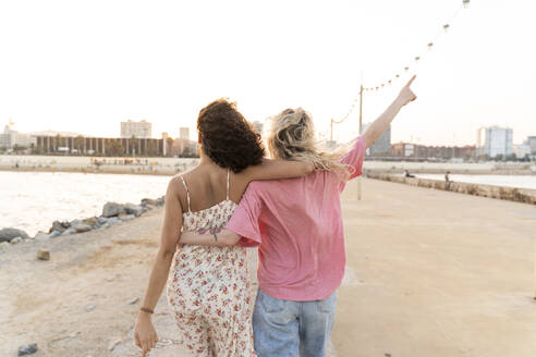 Rear view of two young women on waterfront promenade at sunset - AFVF05516