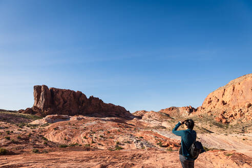 Woman Looking with binoculars out into the desert landscape - CAVF75981