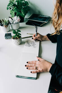 Stock photo of a lettering artist at work with her sketch book. - CAVF76017