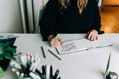 Stock photo of a lettering artist at work with her sketch book. - CAVF76020