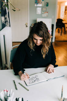 Stock photo of a lettering artist at work with her sketch book. - CAVF76023