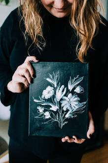 Stock photo of an artist holding up her work. - CAVF76032