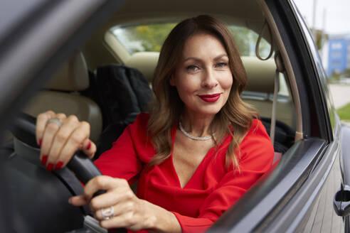 Portrait of smiling mature woman in car - PNEF02457
