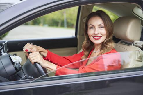 Portrait of smiling mature woman in car - PNEF02472