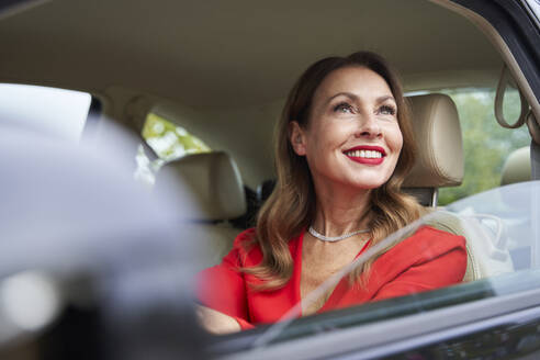 Portrait of smiling mature woman looking out of car window - PNEF02475