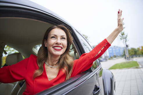 Portrait of happy mature woman looking out of car window waving - PNEF02478