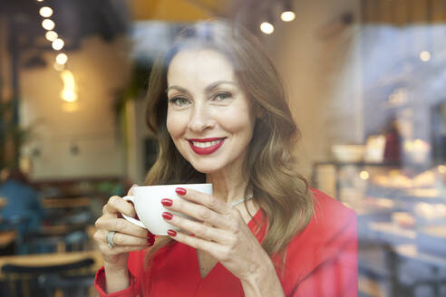 Portrait of smiling mature woman with cup of coffee behind windowpane - PNEF02481