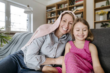 Portrait of happy mother and her little daughter sitting together on the couch having fun - VYF00003