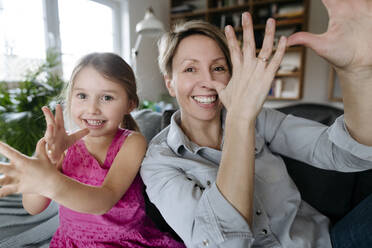 Portrait of happy mother and her little daughter sitting together on the couch having fun - VYF00006