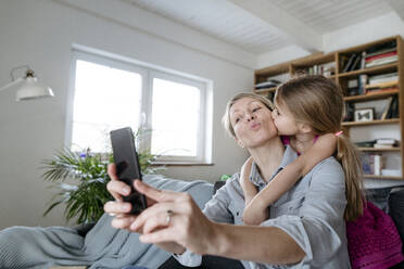 Mother and little daughter taking selfie with smartphone at home - VYF00009