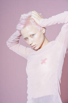 Portrait of young woman with short pink hair wearing pink top in front of pink background - VPIF02104