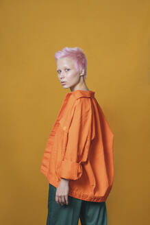 Portrait of young woman with short pink hair wearing orange jacket in front of yellow background - VPIF02110