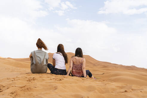 Rear view of three young women sitting in sand dune in Sahara Desert, Merzouga, Morocco - AFVF05528