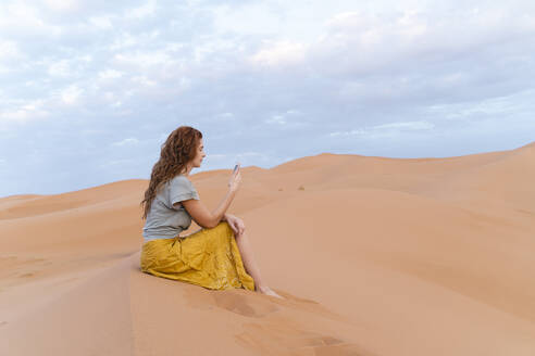 Young woman sitting in sand dune in Sahara Desert using cell phone, Merzouga, Morocco - AFVF05534