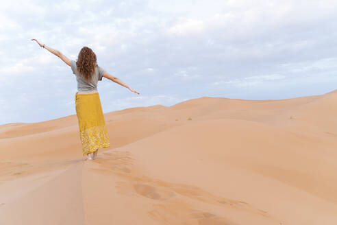 Young woman standing on sand dune in Sahara Desert with outstretched arms, Merzouga, Morocco - AFVF05537