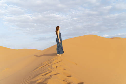 Young woman standing on sand dune in Sahara Desert, Merzouga, Morocco - AFVF05549