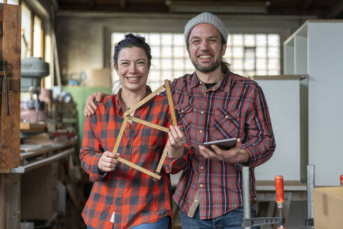 Portrait of happy craftswoman and craftsman holding tablet and yardstick in their workshop - MOEF02835