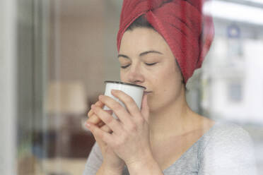 Portrait of woman with head wrapped in a towel drinking a coffee behind windowpane - MOEF02853