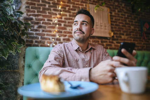 Portrait of a man in a cafe holding cell phone - KIJF02943
