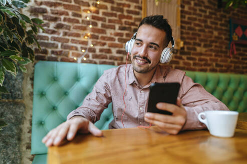Smiling man in a cafe listening to music with headphones - KIJF02946