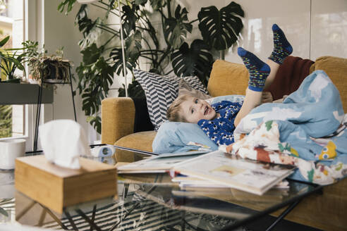 Sick little boy lying on couch at home having fun - MFF05070
