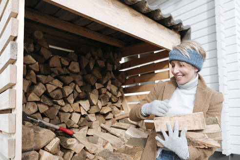 Portrait of smiling mature woman carrying firewood - VYF00013