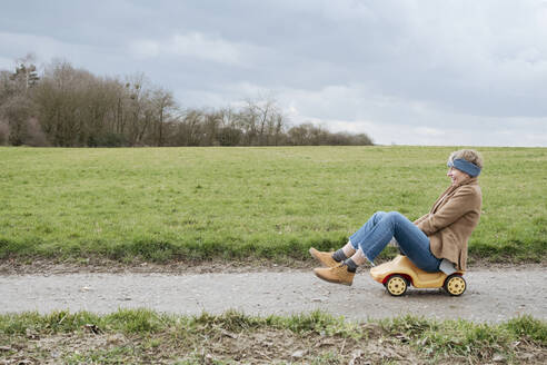 Laughing mature woman riding  bobby car - VYF00016