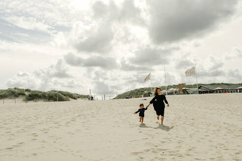 Mother and little daughter running hand in hand on the beach, The Hague, Netherlands - OGF00162