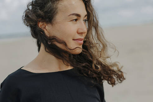 Portrait of smiling woman with blowing hair on the beach - OGF00165