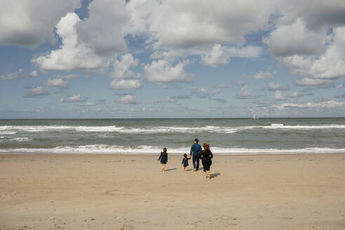 Back view of family with two children walking barefoot on the beach, Scheveningen, Netherlands - OGF00168