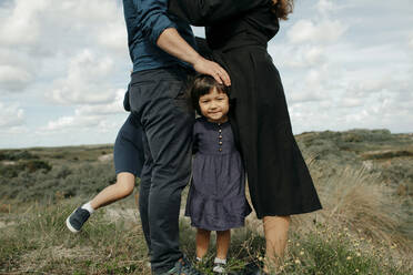Portrait of little girl standing between father and mother in the dunes, The Hague, Netherlands - OGF00178
