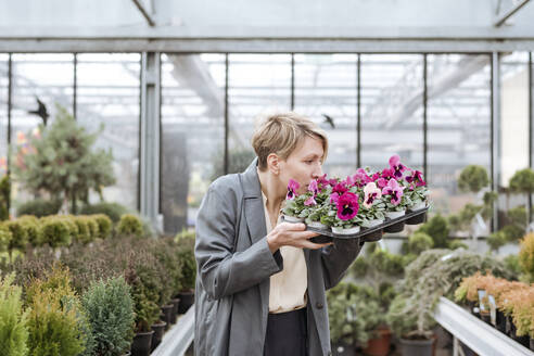 Smiling woman with pansies in flower shop - VYF00024