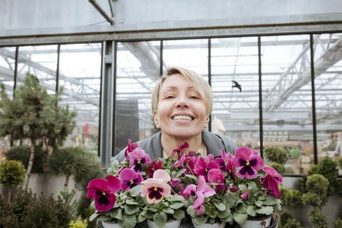 Smiling woman with pansies in flower shop - VYF00027