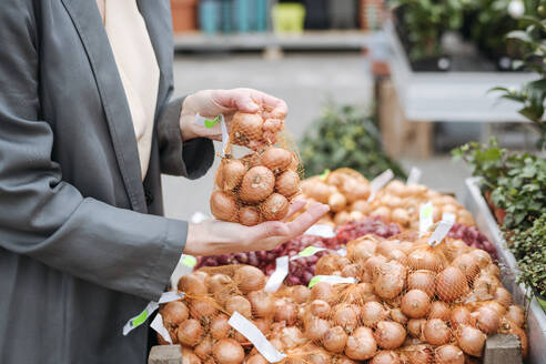 Woman's hands holding onion packing - VYF00030