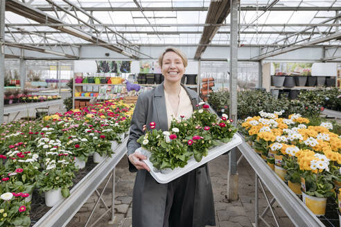 Smiling woman holding daisies in flower shop - VYF00033