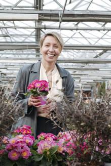 Woman choosing pottetd flowers in flower shop - VYF00036