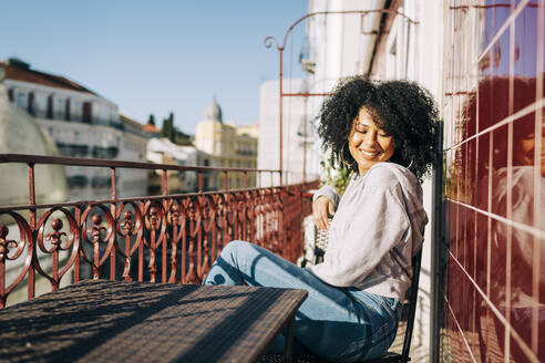 Happy young woman with curly hair sitting on balcony enjoying the sunshine - DCRF00079