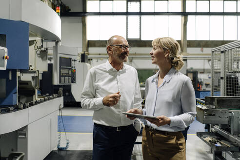 Man and woman with tablet talking in a factory - KNSF07704