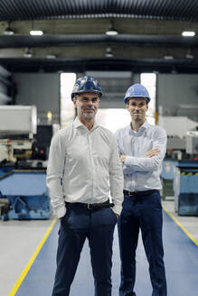 Portrait of two confident men wearing hard hats in a factory - KNSF07713