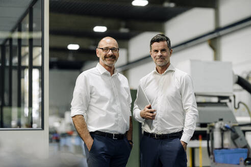 Portrait of two confident businessmen in a factory - KNSF07731