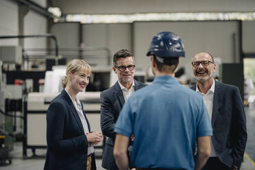 Smiling business people looking at worker in a factory - KNSF07740