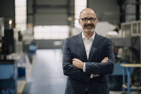 Portrait of a confident businessman in a factory - KNSF07749