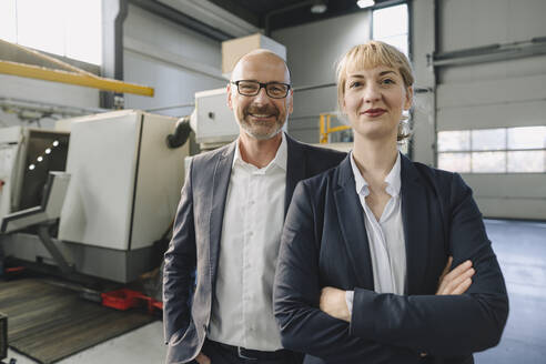 Portrait of confident businessman and businesswoman in a factory - KNSF07770